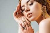 young tender naked woman with shiny makeup, golden rings and earrings in turban isolated on grey