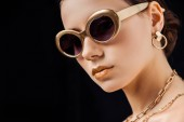 young naked woman in sunglasses, golden earring and necklaces looking at camera isolated on black