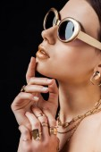 young nude woman in sunglasses, golden earring, rings and necklaces isolated on black