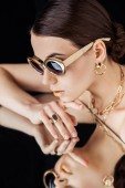 young naked woman in sunglasses, golden accessories lying on mirror isolated on black