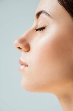 profile of young woman with closed eyes, shiny lips and golden eye shadow isolated on grey