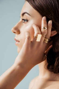 profile of young woman with golden rings isolated on grey