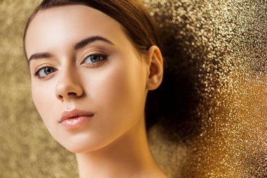 Young beautiful woman with shiny makeup looking at camera on golden textured background stock vector