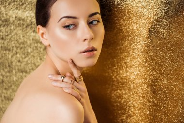 Nude young woman with shiny makeup and golden rings looking away on golden textured background stock vector