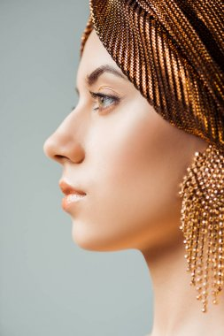 Profile of young woman with shiny make up, turban and golden earring isolated on grey stock vector