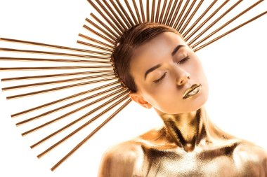 nude young woman painted in golden with accessory on head and closed eyes isolated on white