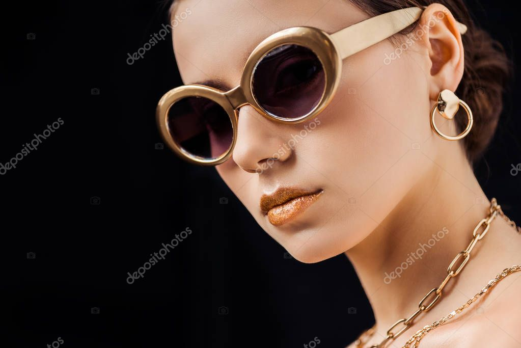Young naked woman in sunglasses, golden earring and necklaces looking at camera isolated on black stock vector