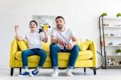 Fotografie Aufgeregter Sohn jubelt beim Videospiel mit Vater auf der heimischen Couch