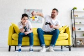 father showing thumb down while sitting with son and playing Video Game at home