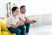 otec a syn hrají video hru na gauči v obývacím pokoji s prostorem pro kopírování