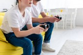 vista cropped di padre e figlio giocare videogioco sul divano in salotto