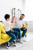 otec a syn hrají při hraní video hry na gauči s velkým pěti pohyby
