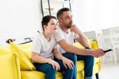 Fényképek apa és fia ül a kanapén, és tévénézés otthon