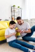 otec a syn sedí na koberci a používají smartphone v obývacím pokoji