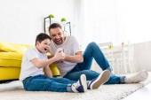 aufgeregt Vater und Sohn sitzen auf Teppich und mit Dem Smartphone im Wohnzimmer