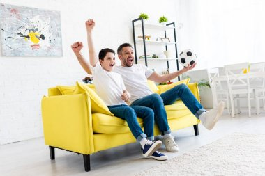 excited father and son cheering and watching sports match on couch in Living Room