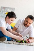 father and son sitting on carpet and playing with toy car at home in Living Room
