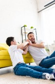 son taking away smartphone from laughing father in Living Room