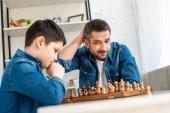 messa a fuoco selettiva di padre e figlio in denim giocare a scacchi a casa