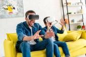 vzrušený otec a syn ve VR hlavní reality na gauči doma