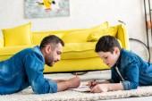 Vater und Sohn liegen auf Teppich und Zeichnen im Wohnzimmer
