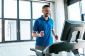 schön lächelndmann Training auf Laufband im Fitnessstudio mit Kopierplatz