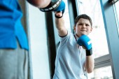 Fotografie selective focus of boy in boxing gloves training with coach at gym