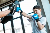 boy in boxing gloves working out with coach at gym