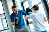boy in boxing gloves working out with father at gym