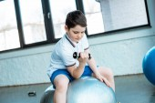 cute boy sitting on fitness ball and working out with dumbbell at gym