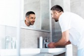 handsome smiling man looking in mirror and washing hands in bathroom during morning routine