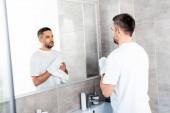 jóképű férfi törlőkő kezet törülközővel a fürdőszobában reggel