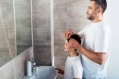 otec v noci upravováním účesu syna v koupelně