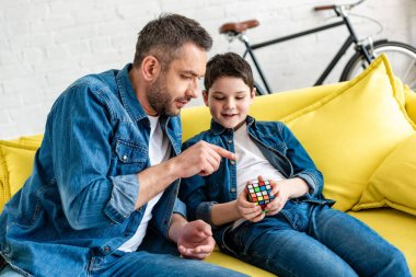 father sitting on couch with son and pointing with finger at toy cube