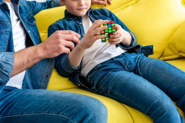 cropped view of father and son sitting on couch and playing with toy cube at home