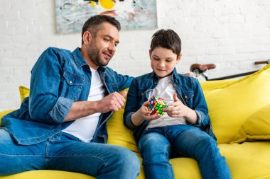 father and son sitting on couch and playing with toy cube at home
