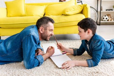 father and son lying on carpet with color pencils in Living Room