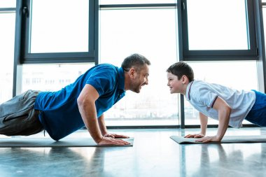father and son looking at each other while doing push up exercise at gym