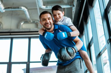 happy father giving piggyback ride to happy son in boxing gloves at gym