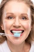 žena středního věku s oprašným úsměvem kartáčováním zubů izolovaných na bílém
