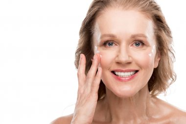 mature woman applying cosmetic cream on face Isolated On White