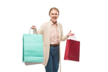 happy middle aged woman with shopping bags looking at camera Isolated On White