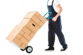 cropped view of delivery man in overalls transporting hand truck loaded with cardboard boxes isolated on white