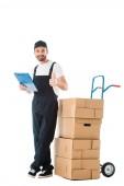 felice uomo consegna in piedi vicino camion mano con scatole di cartone e mostrando pollice in su isolato su bianco