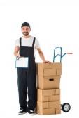 uomo di consegna sorridente che tiene gli appunti con schermo bianco mentre in piedi vicino camion a mano caricato con scatole di cartone isolate su bianco