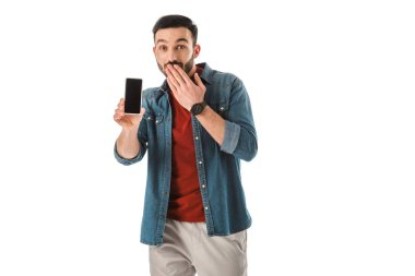 surprised bearded man covering mouth with hand while holding smartphone with blank screen isolated on white