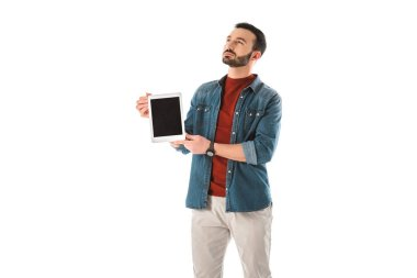 Pensive bearded man looking up while holding digital tablet with blank screen isolated on white stock vector
