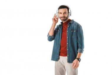positive smiling man listening music in headphones and looking at camera isolated on white