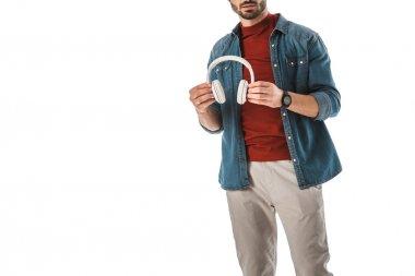 adult man in denim shirt holding headphones isolated on white