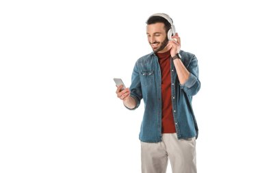cheerful man listening music in headphones and using smartphone isolated on white